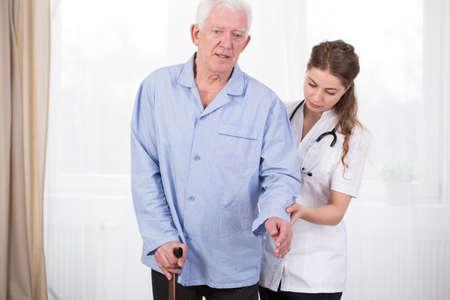 患者の医者によって補助杖を使用