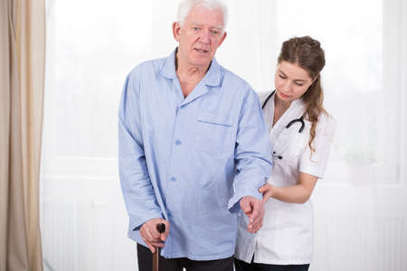 assisted: Patient using walking stick assisted by doctor
