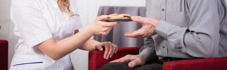 apoyo social: Primer plano de auxiliar de atención que dan galletas pensionista