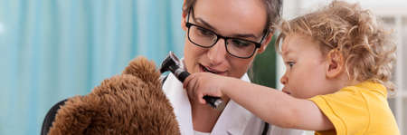 kid at doctor: Little boy using otoscope to examine bears ear