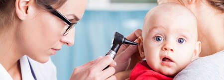Pediatrician using otoscope to examine babys ear