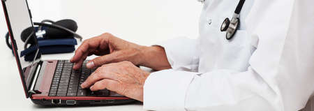 office use: Close-up of doctor using laptop at work