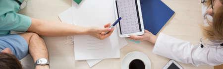 consulta médica: Equipo médico sentado en la mesa y analizar cardiograma Foto de archivo