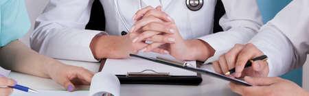 consulta médica: Equipo médico sentado en la mesa - panorama