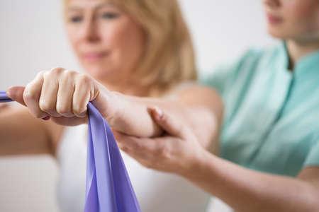 fisioterapia: Entrenamiento de la mujer con la banda de ejercicio durante la rehabilitación