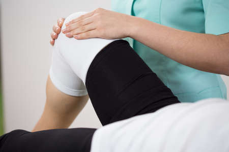 Orthopedic diagnosing painful knee of young woman