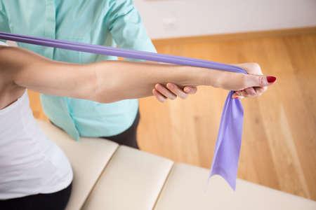 física: Primer plano de la paciente hace ejercicio con banda elástica