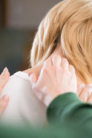 treating: Osteopath treating painful neck of young woman