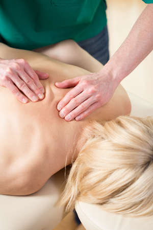 kneading: Vertical view of masseur kneading back muscles