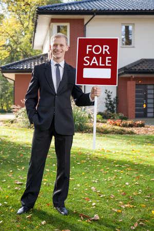 investment real state: Agente Feliz raíces de pie en frente de la casa