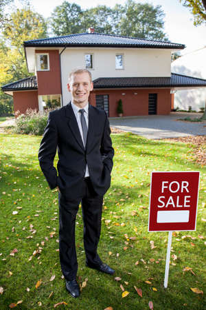 Estate broker is standing outside the house and smiling photo