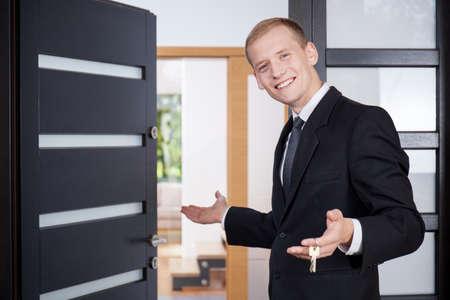 Jonge makelaar nodigt klanten naar huis te bekijken Stockfoto