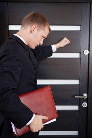 tocar la puerta: Joven agente inmobiliario antes de entrar en el edificio