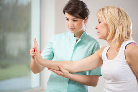 fisico: Mujer rubia durante la rehabilitaci�n despu�s de una lesi�n de mu�eca Foto de archivo