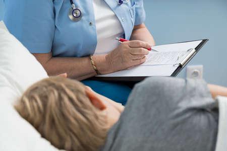 medico pediatra: Escritura femenina del doctor por sus notas sobre niño pequeño Foto de archivo