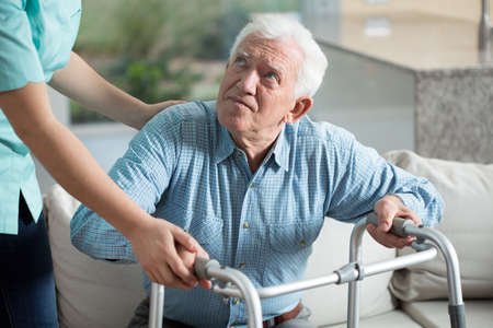 assisting: Disabled senior man being in nursing home Stock Photo