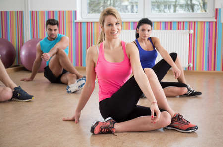 fitness: Photo of fit people stretching legs during fitness classes Stock Photo