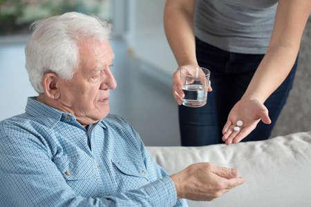 薬を飲んで病気の年配の男性人のクローズ アップ