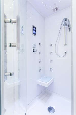 Photo of modern white shower in new luxury bathroom photo