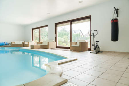 gym room: Big gym with swimming pool at luxury home Stock Photo