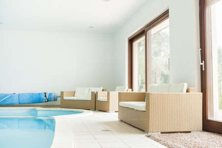 pool room: Bright relax room with big swimming pool and comfortable chairs Stock Photo