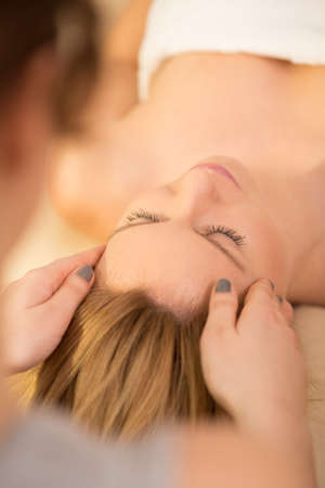 Close-up of woman relaxing during head massage
