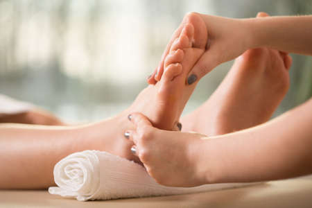 woman foot: Close-up of female hands doing foot massage Stock Photo