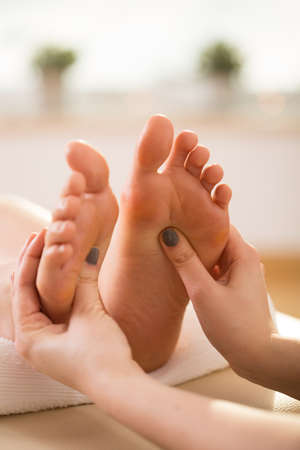 Therapist pressing on reflex areas on the feet