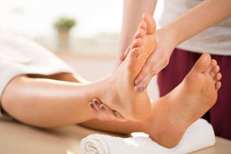 masajes relajacion: Vista horizontal de masajista haciendo masaje de piernas Foto de archivo