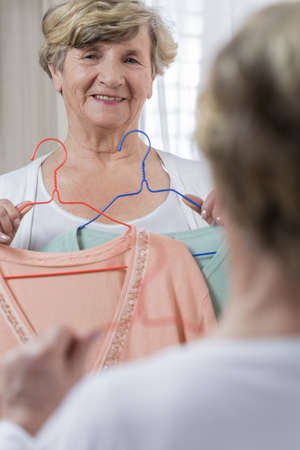 Senior woman choosing sweater before important meeting