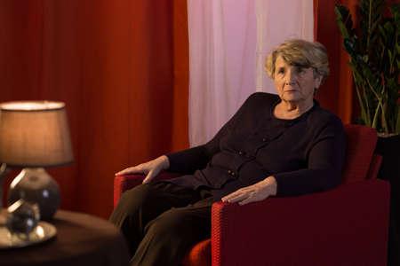 Melancholic senior woman being alone at home