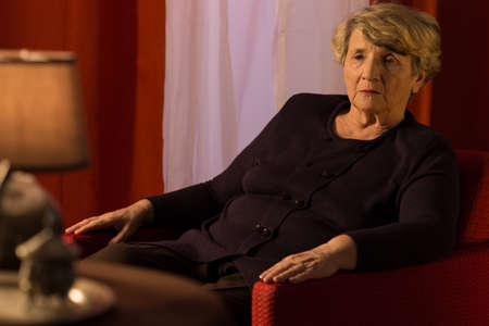 Lonely depressed retiree sitting in armchair and thinking
