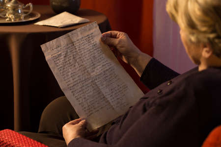widow: Senior woman reading yellowed letter from a lover Stock Photo