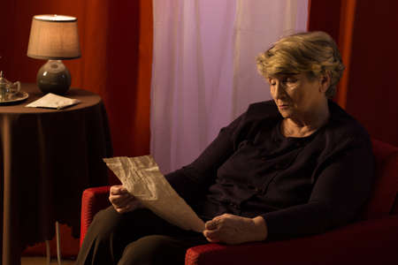 Melancholic retiree sitting in armchair and reading old letter