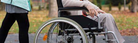 車椅子で公園で看護師女性