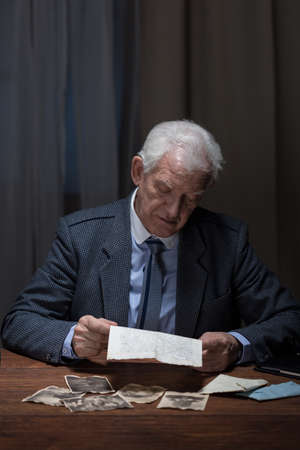 reminisce: Lonely sad businessman reading letter and looking at photos