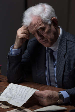 Lonely aged man reading old letter from a lover photo