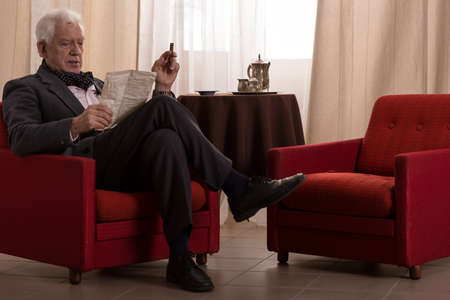 Old millionaire sitting in an armchair and smoking cigar 스톡 콘텐츠