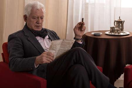 hombre fumando puro: Hombre mayor leyendo vieja carta y fumar cigarros