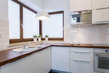Encimeras de madera y armarios blancos en la cocina tradicional Foto de archivo - 38014648
