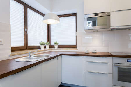 Wooden countertops and white cupboards in traditional kitchen Stock Photo