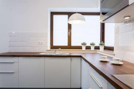木製の調理台と高級キッチンのホワイトの食器棚 写真素材 - 38014688