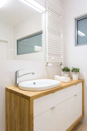 Close-up of washbasin situated in wooden cupboard