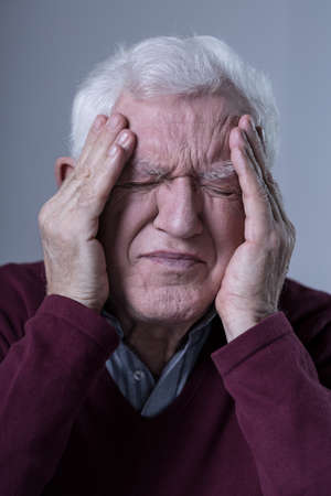 acute: Aged sad man with acute pain in his head Stock Photo