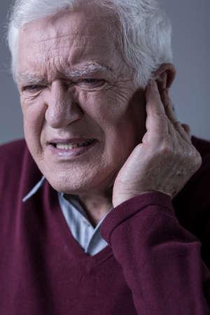 dolor de oido: Hombre elegante mayor con el dolor de o�do agudo