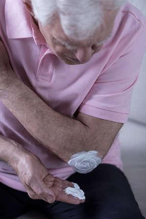 Aged man using his painkiller cream