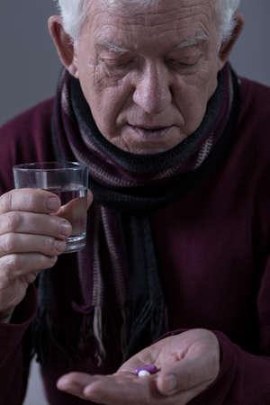 Elderly sick man taking his pills