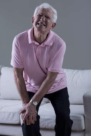 Senior man in vreselijke pijn met gewonde knie Stockfoto