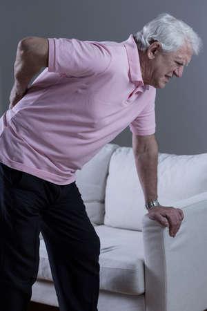 personne malade: Senior homme avec soutien lombaire douloureux discopathie