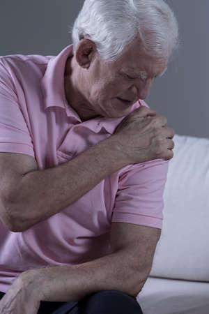epaule douleur: Homme triste principal avec la douleur aigu� dans son articulation de l'�paule Banque d'images